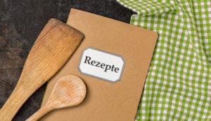 Bild: Rezeptbuch mit Kochlöffel und Küchentuch