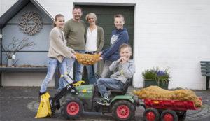 Bild: Familien hält Kartoffelsack, Kind davor auf Spielzeugtraktor mit Kartofelsack auf Anhänger