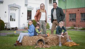 Bild: Familie vor Hof, Kinder sitzen auf Strohballen umgeben von Kartoffeln im Sack und Eimer